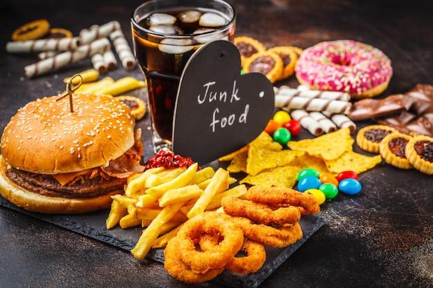 Фаст фуд и сахар. бургер, сладости, чипсы, шоколад, пончики, сода. Premium Фотографии