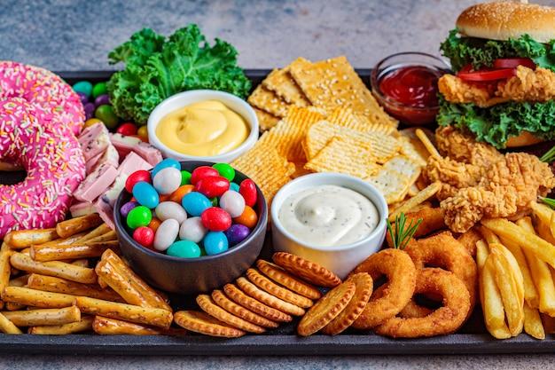 ファーストフードの品揃え。ジャンクフードのコンセプトです。心臓、歯、皮膚、体に不健康な食べ物。 Premium写真