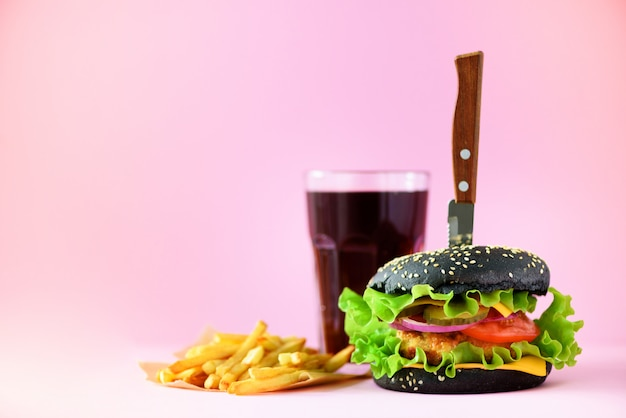 Fast food banner. juicy meat burgers with cheese, lettuce on pink background. take away meal. unhealthy diet concept with copy space Premium Photo