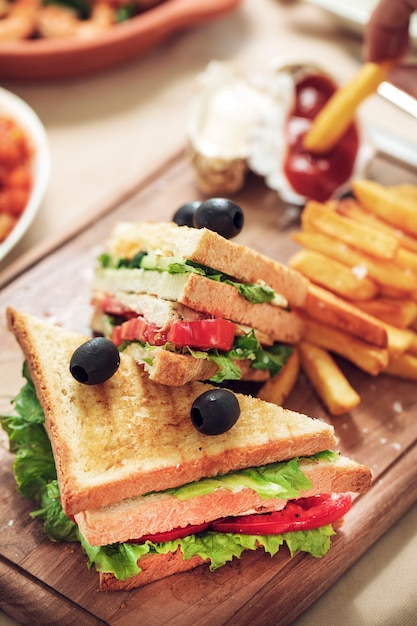 Fast food board with club sandwiches and french fries. Free Photo