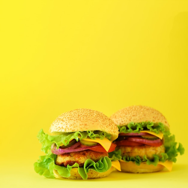 Fast food concept. square crop. juicy homemade hamburgers on yellow background. take away meal. unhealthy diet frame Premium Photo