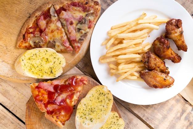 ファーストフード、クリスピーチキンウイング、パン、フレンチフライ、ピザ Premium写真
