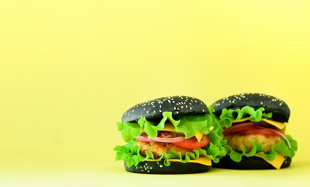 Fast food frame. delicious meat burgers on yellow background. take away meal. unhealthy diet concept with copy space Premium Photo