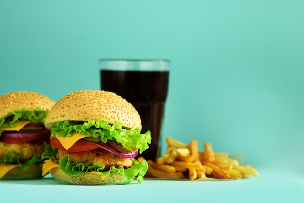 Fast food - juicy hamburger, french fries potatoes and cola drink on blue background. take away meal. unhealthy diet concept with copy space Premium Photo