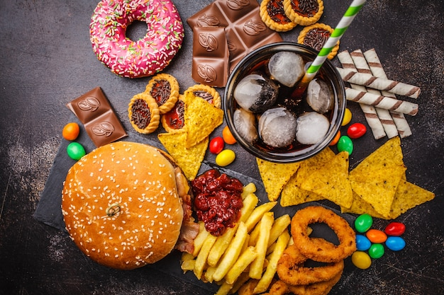 Fast food and sugar. burger, sweets, chips, chocolate, donuts, soda, top view. Premium Photo