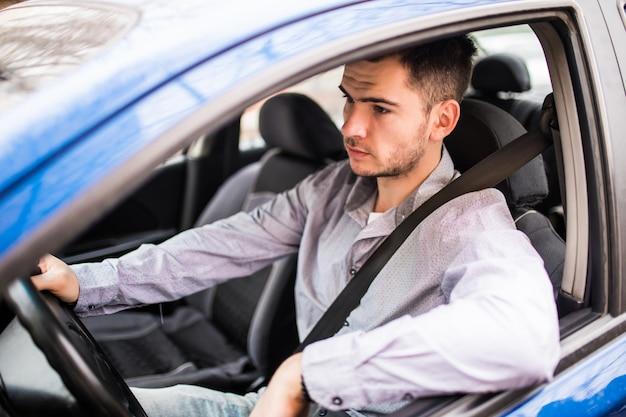 カーシートベルトを締めます。運転中の若い男の安全ベルトの安全性 無料写真