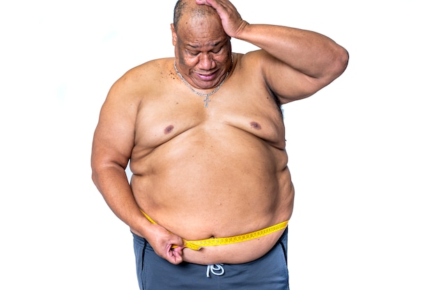 Fat black man measures his waist with a tape measure to see if he has lost weight with the regime Premium Photo