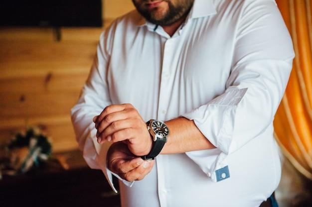 手首にスタイリッシュな時計バンドを握り締める太った新郎 Premium写真