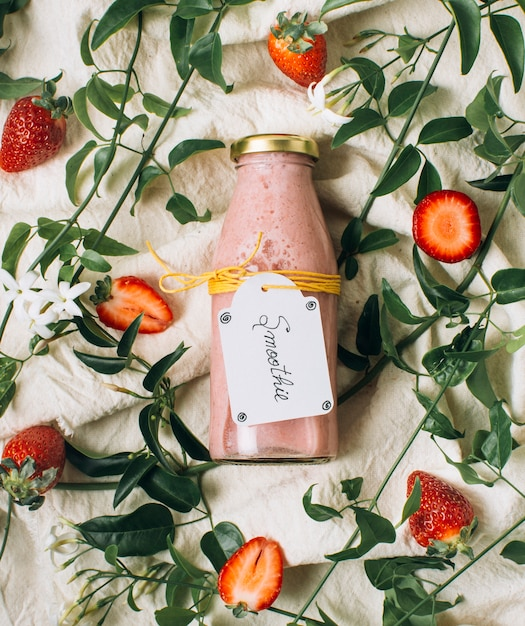 Fat lay pink smoothie next to strawberries Free Photo