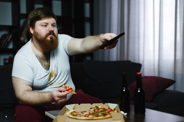 Fat man eats pizza sitting on the sofa and switches channels on the tv-set Free Photo