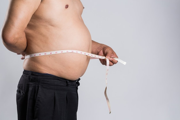 Fat man is measuring belly with measuring tape Premium Photo
