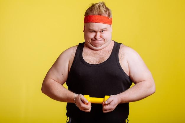 Толстяк пытается поднять маленький желтый гантель Premium Фотографии