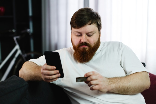 Fat man types the number of a credit card in his phone sitting on the couch Free Photo
