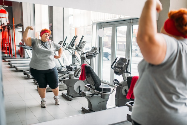 체육관에서 거울에 대 한 훈련 지방 땀에 젖은 여자. 칼로리 연소, 스포츠 클럽에서 뚱뚱한 여성 사람 프리미엄 사진