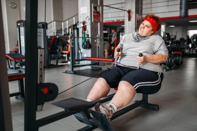 뚱뚱한 여자, 체육관에서 운동 기계에 대한 적극적인 훈련. 칼로리 연소, 스포츠 클럽에서 뚱뚱한 여성 사람 프리미엄 사진