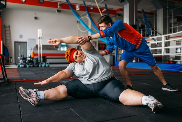 뚱뚱한 여자, 강사와 함께 바닥에 운동, 체육관에서 운동. 칼로리 연소, 스포츠 클럽에서 뚱뚱한 여성 사람 프리미엄 사진