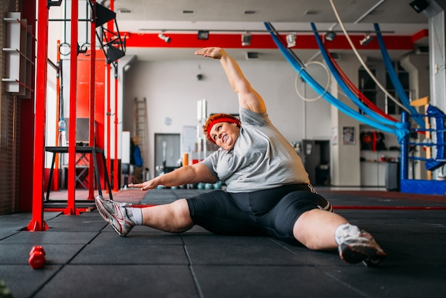 뚱뚱한 여자는 바닥에 운동, 체육관에서 운동 프리미엄 사진