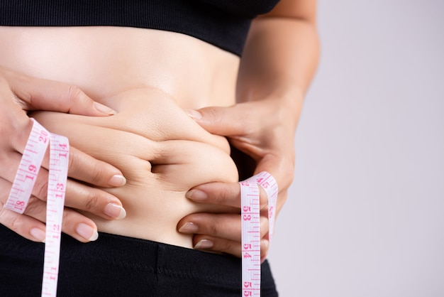 Fat woman hand holding excessive belly fat with measuring tape. Premium Photo