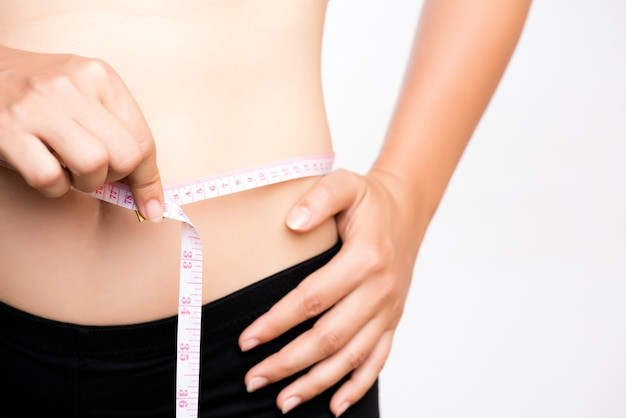 Fat woman hand measuring waist with white measuring tape Premium Photo