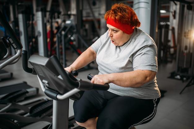 체육관에서 운동 자전거에 뚱뚱한 여자 훈련. 칼로리 연소, 스포츠 클럽에서 뚱뚱한 여성 사람 프리미엄 사진