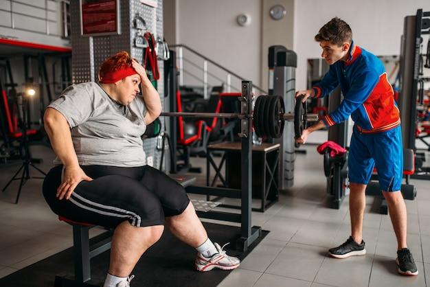 바벨을 사용하는 뚱뚱한 여자, 강사와 함께 훈련 프리미엄 사진