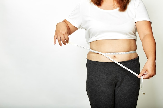 Fat woman with measure tape Premium Photo