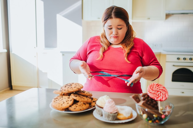 Fat young woman in kitchen sitting and eating sweet food Premium Photo