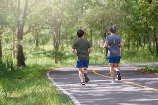 Father and adult son jogging on the park path Premium Photo