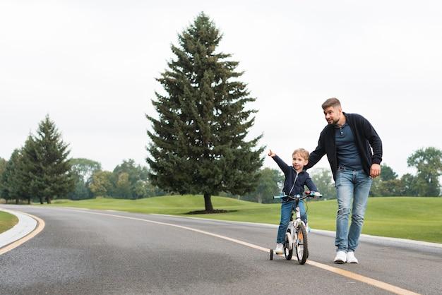아버지와 자전거와 함께 공원에서 노는 아이 무료 사진