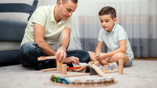 Отец и ребенок играют с игрушками в спальне Бесплатные Фотографии