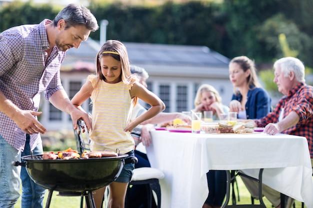 家族が昼食をとりながらバーベキューグリルで父と娘 Premium写真