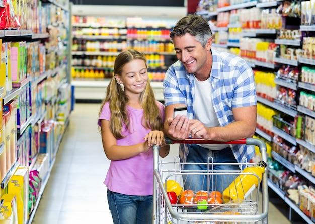스마트 폰을 사용 하여 슈퍼마켓에서 아버지와 딸 프리미엄 사진