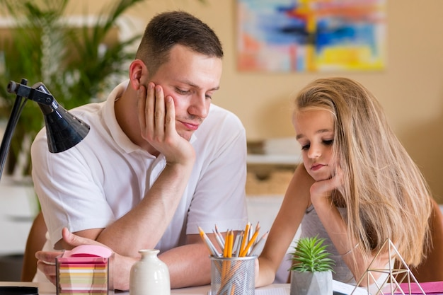 Отец и дочь скучают и делают домашнее задание Бесплатные Фотографии