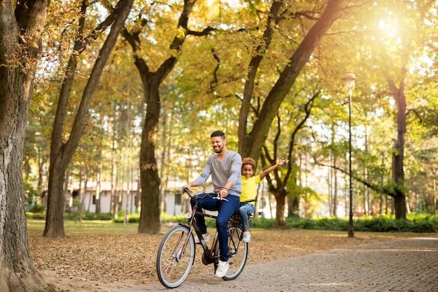 自然の中で自転車に乗ることを楽しんでいる父と娘 無料写真