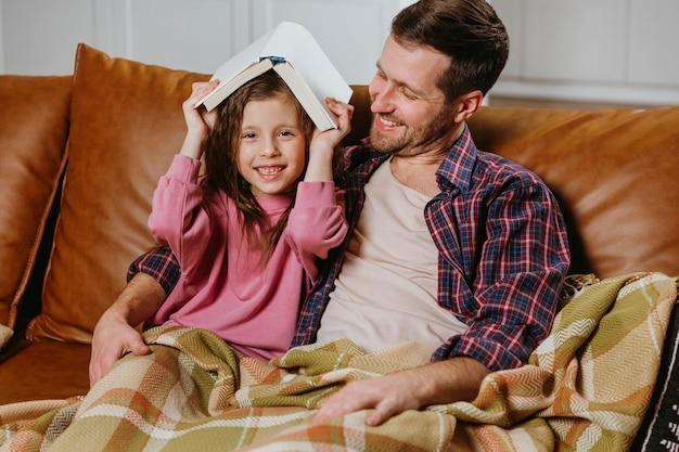 父と娘が一緒に家で本を読んでいます 無料写真