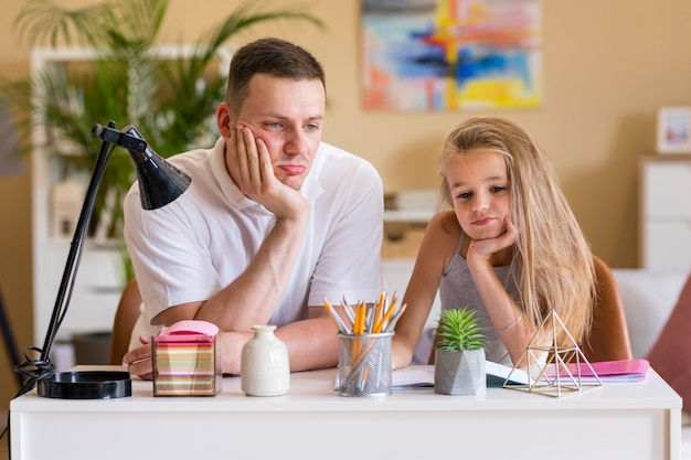 Отец и дочь сидят за столом Бесплатные Фотографии