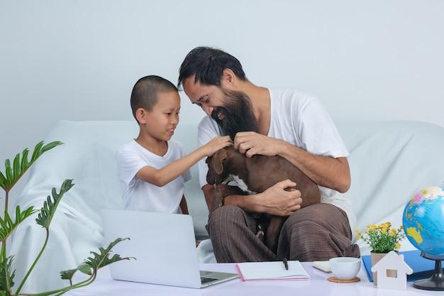 父と子供は自宅のソファーで作業しながら犬を遊んでいます。 無料写真