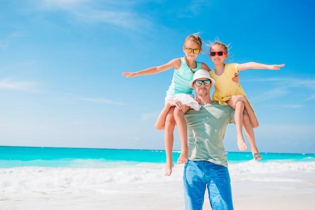 Отец и дети наслаждаются летними каникулами на пляже Premium Фотографии