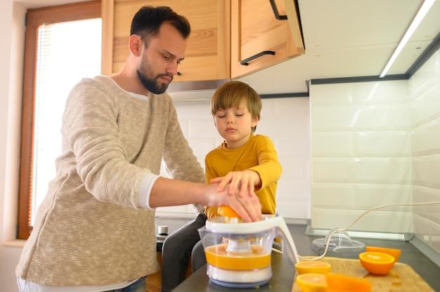 Отец и сын сосредоточены на создании апельсинового сока Бесплатные Фотографии