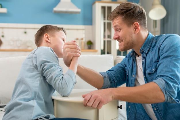 Отец и сын занимаются армрестлингом Бесплатные Фотографии