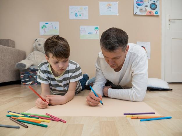 Отец и сын рисуют вместе на полу Бесплатные Фотографии