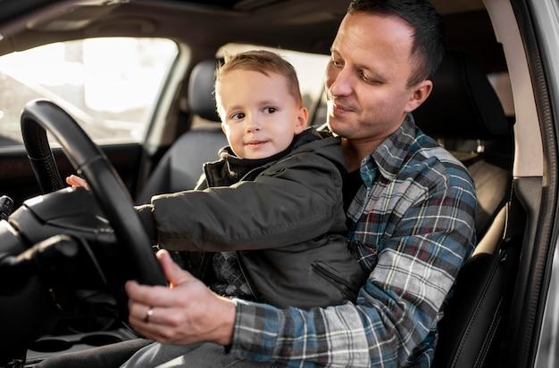 Отец и сын едут вместе Premium Фотографии