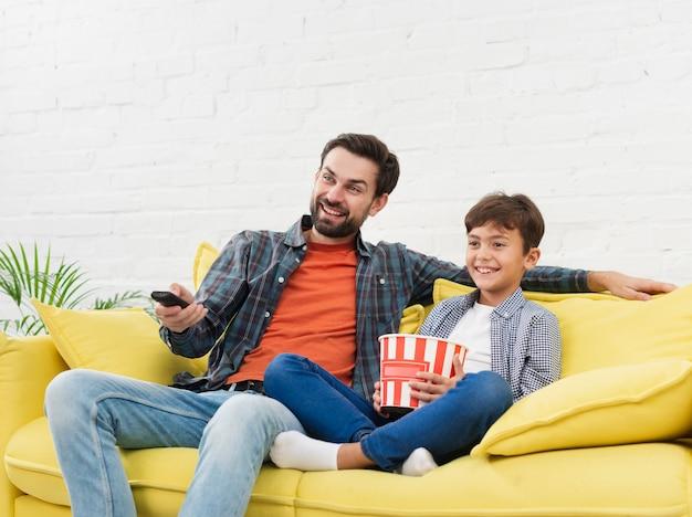 Отец и сын едят попкорн и смотрят телевизор Premium Фотографии