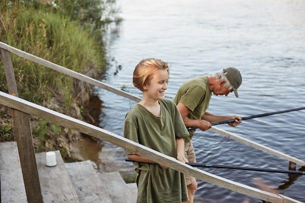 父と息子が一緒に釣りに、水につながる木製の階段の上に立って 無料写真