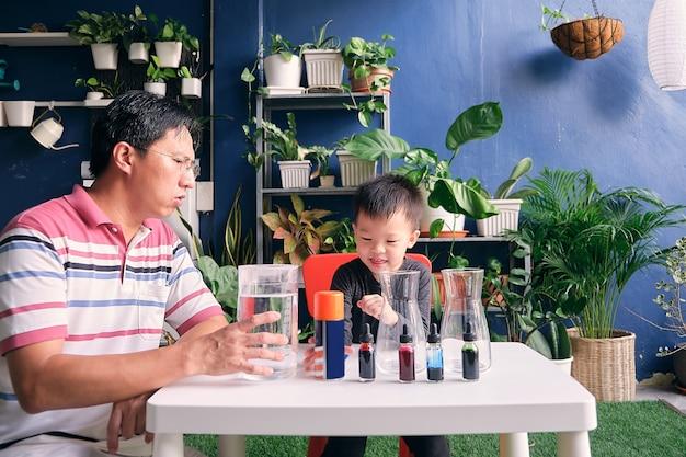 簡単な科学実験の準備を楽しんでいる父と息子 Premium写真