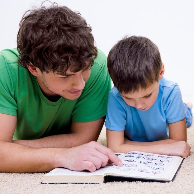 Отец и сын в помещении, читая книгу, лежа на полу Бесплатные Фотографии