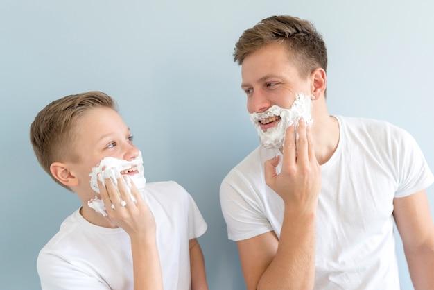 Отец и сын похожи друг на друга с кремом для бритья Бесплатные Фотографии