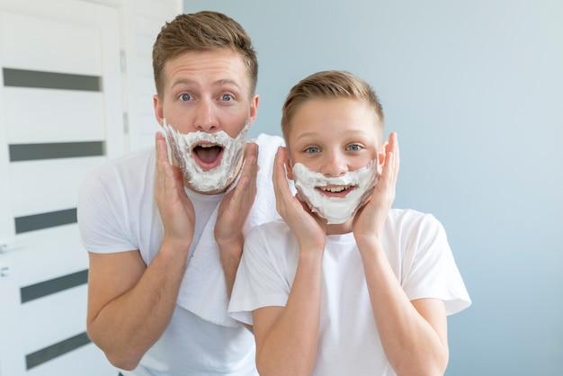 Отец и сын выглядят смешно с пеной для бритья Бесплатные Фотографии