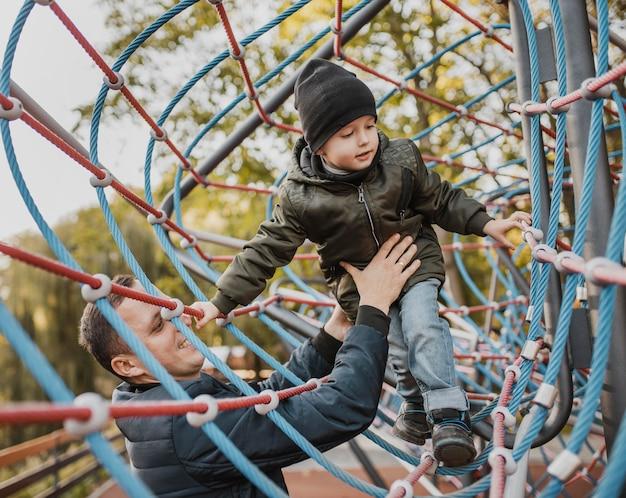 Отец и сын играют в парке Premium Фотографии