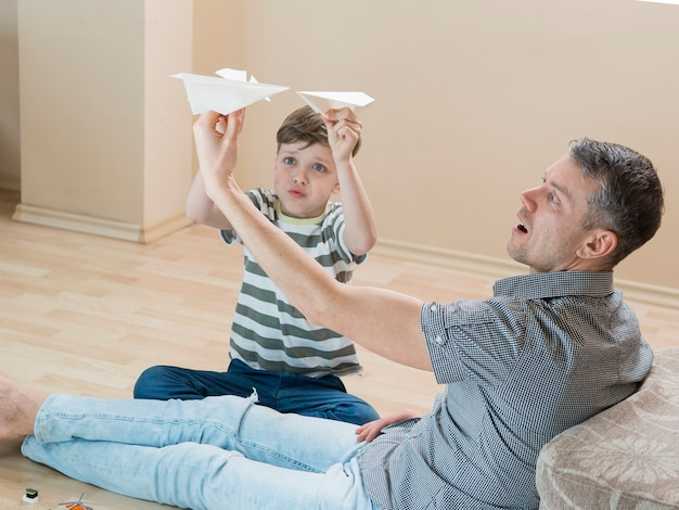 Отец и сын играют в помещении с бумажными самолетиками Бесплатные Фотографии